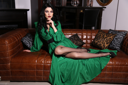 luxurious interior: fashion interior photo of beautiful sensual woman with dark hair wears elegant green dress, posing on leather divan