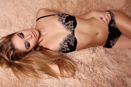 mujer elegante: Foto de la moda interior de la mujer hermosa del encanto con el pelo rubio en ropa interior elegante que presenta en el dormitorio