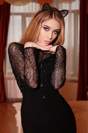 oido: de fotografía de moda interior de la mujer hermosa del encanto con el pelo rubio en un elegante vestido negro y los oídos del conejito diadema ,, posando en el dormitorio Foto de archivo