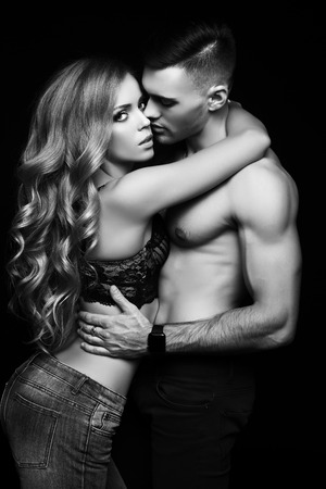 sexy photo: fashion black and white studio photo of beautiful couple with sportive sexy bodies, gorgeous woman with long blond hair embracing handsome brunette man