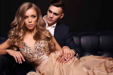gorgeous woman: fashion studio photo of beautiful couple in elegant clothes, gorgeous woman with long blond hair posing with handsome brunette man Stock Photo