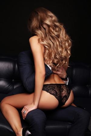 fashion studio foto van mooie paar. prachtige vrouw met lang blond haar omarmen knappe brunette man