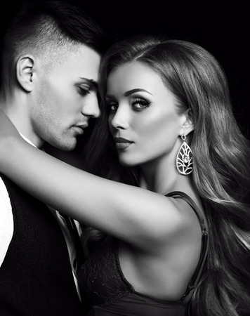 gorgeous: fashion black and white studio photo of beautiful couple in elegant clothes, gorgeous woman with long blond hair embracing handsome brunette man Stock Photo
