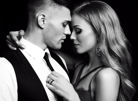 fashion black and white studio photo of beautiful couple in elegant clothes, gorgeous woman with long blond hair embracing handsome brunette man Stock Photo