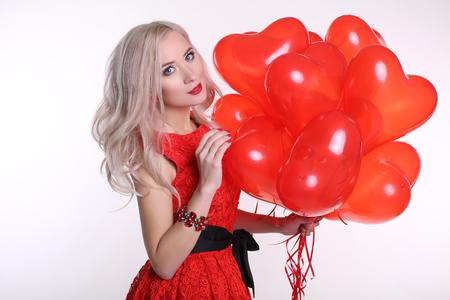 cabello rubio: foto de estudio de moda de mujer hermosa con el pelo rubio lleva elegante vestido rojo, sosteniendo un montón de globos de aire color rojo en forma de corazón