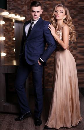studio photo de mode de la belle couple dans des vêtements élégants, magnifique femme avec de longs cheveux blonds embrassant bel homme brune