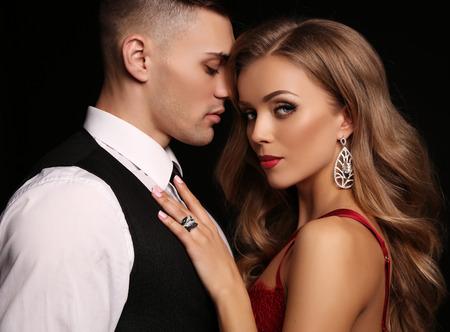 foto de estudio de la moda de la bella pareja en ropa elegante, hermosa mujer con pelo largo y rubio que abraza Morena guapo