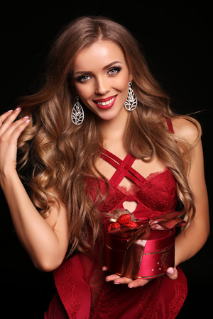 red corset: fashion studio photo of gorgeous sexy woman with long blond hair wears elegant red lingerie corset, smiling and holding present box Stock Photo
