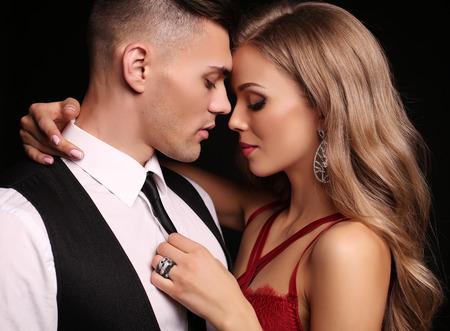 foto de estudio de la moda de la bella pareja en ropa elegante, hermosa mujer con pelo largo y rubio que abraza Morena guapo Foto de archivo