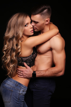 fashion studio photo of beautiful couple with sportive sexy bodies, gorgeous woman with long blond hair embracing handsome brunette man Stock Photo