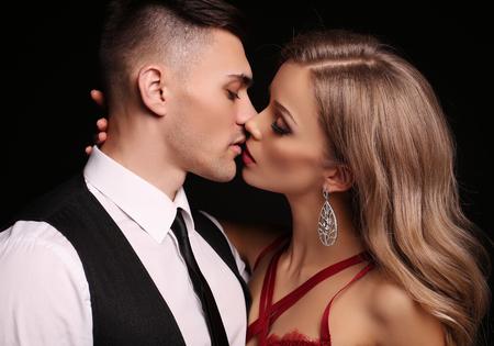 エレガントな服の美しいカップル、長いブロンドの髪がブルネットのハンサムな男をキスでゴージャスな女性のファッション スタジオ写真