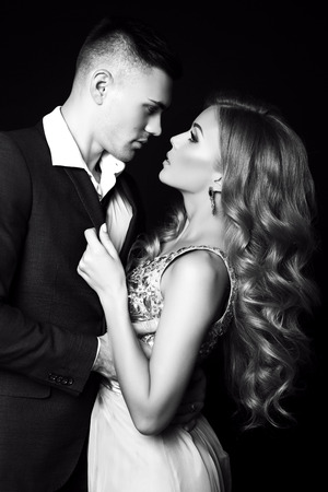 hair man: fashion black and white studio photo of beautiful couple in elegant clothes, gorgeous woman with long blond hair embracing handsome brunette man Stock Photo