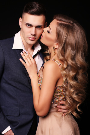 embracing couple: fashion studio photo of beautiful couple in elegant clothes, gorgeous woman with long blond hair embracing handsome brunette man