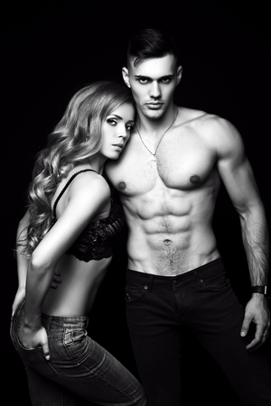 woman muscle: fashion black and white studio photo of beautiful couple with sportive sexy bodies, gorgeous woman with long blond hair embracing handsome brunette man