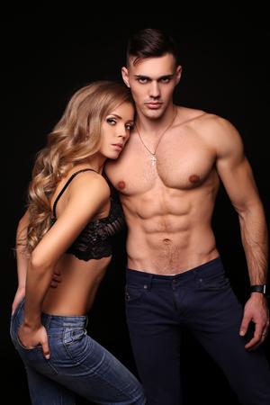 fashion studio foto van mooie paar met sportieve sexy lichamen, prachtige vrouw met lang blond haar omarmen knappe brunette man