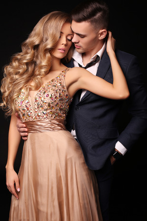 blond hair: fashion studio photo of beautiful couple in elegant clothes, gorgeous woman with long blond hair embracing handsome brunette man