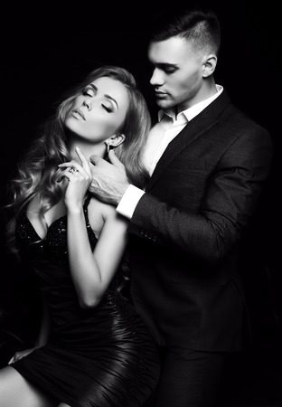 passion couple: fashion studio photo of beautiful couple in elegant clothes, gorgeous woman with long blond hair embracing handsome brunette man