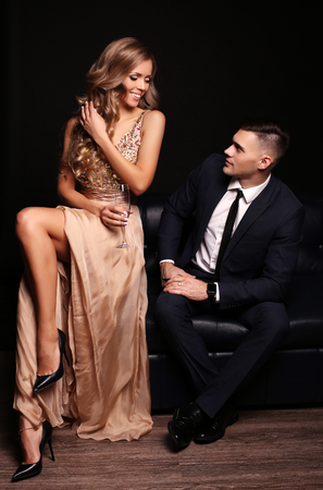 elegant party: fashion studio photo of beautiful couple in elegant clothes, gorgeous woman with long blond hair embracing handsome brunette man