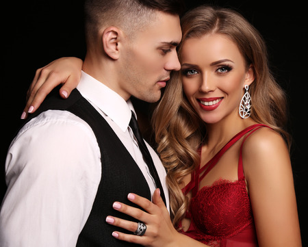 love story: fashion studio photo of beautiful couple in elegant clothes, gorgeous woman with long blond hair embracing handsome brunette man