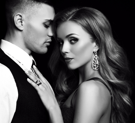 fashion black and studio photo of beautiful couple in elegant clothes, gorgeous woman with long blond hair embracing handsome brunette man Stockfoto