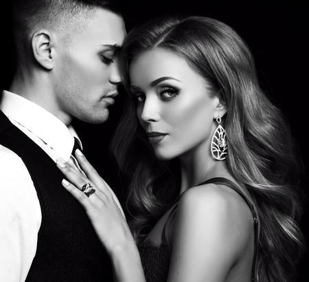 fashion zwart en studio foto van mooie paar in elegante kleren, prachtige vrouw met lang blond haar omarmen knappe brunette man Stockfoto