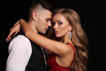 Mode Studio Foto der schönen Paar in elegante Kleidung, wunderschöne Frau mit langen blonden Haaren umarmen gut aussehend Brunettemann Standard-Bild - 51693375