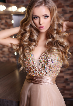 fashion studio photo of gorgeous woman with long blond hair wears luxurious beige dress