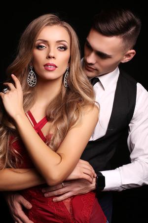 donne eleganti: studio fotografico di moda di bella coppia in abiti eleganti, bellissima donna con lunghi capelli bionda che abbraccia uomo bello bruna Archivio Fotografico