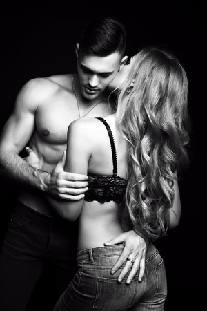 fashion black and white studio photo of beautiful couple with sportive sexy bodies, gorgeous woman with long blond hair embracing handsome brunette man