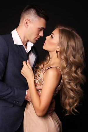 gorgeous woman: fashion studio photo of beautiful couple in elegant clothes, gorgeous woman with long blond hair embracing handsome brunette man