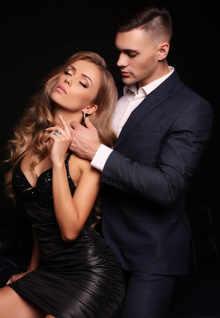 party outfit: fashion studio photo of beautiful couple in elegant clothes, gorgeous woman with long blond hair embracing handsome brunette man