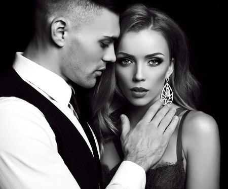 la moda en blanco y negro foto del estudio de la bella pareja en ropa elegante, hermosa mujer con pelo largo y rubio que abraza Morena guapo