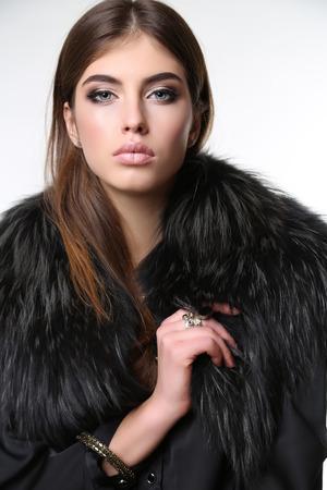 fashion studio photo of gorgeous sensual woman with dark straight hair wears elegant fur coat and bijou