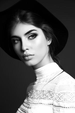 cabello negro: la moda en blanco y negro foto del estudio de la mujer sensual hermosa con el pelo oscuro recto lleva ropa elegante, sombrero negro y bijou