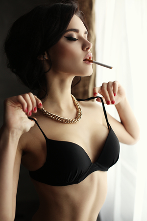 fashion interior photo of beautiful sexy girl with dark hair wears lingerie,smoking beside a window