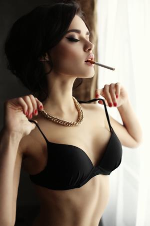 persona fumando: Foto de la moda interior de la muchacha atractiva hermosa con el pelo oscuro se desgasta la ropa interior, fumando junto a una ventana Foto de archivo