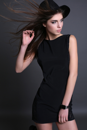 beauty body: fashion studio photo of gorgeous sensual woman with dark straight hair and natural makeup,wears elegant black dress and hat Stock Photo