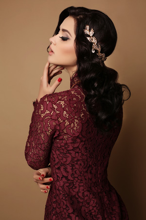 fashion studio photo of beautiful sexy girl with dark hair wears elegant lace dress, luxurious necklace and tiara