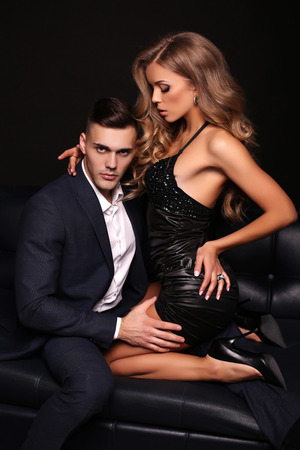 美しいカップルのファッション スタジオ写真。エレガントなスーツを着たハンサムなブルネット男でポーズをとって長いブロンドの髪とゴージャスな女性 写真素材