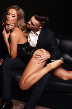 party outfit: fashion studio photo of beautiful couple. gorgeous woman with long blond hair posing with handsome brunette man in elegant suit
