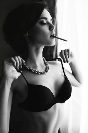 ファッション黒と白の間の窓際喫煙身に着けているランジェリーで黒い髪、美しいセクシーな女の子の写真