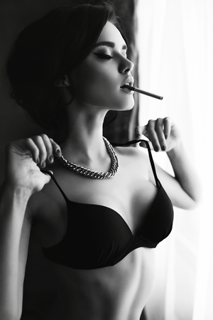 fashion black and white interior photo of beautiful sexy girl with dark hair wears lingerie,smoking beside a window