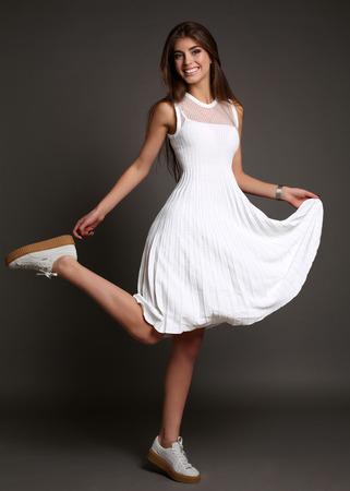 fashion dress: fashion studio photo of gorgeous sensual woman with dark straight hair wears elegant white dress and shoes