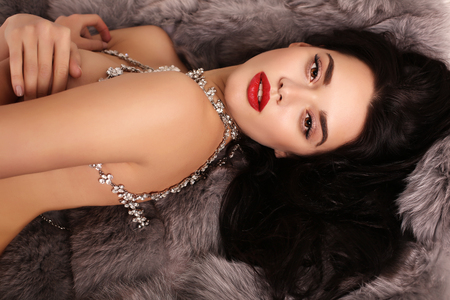 fashion interior photo of beautiful sexy girl with dark hair with luxurious bijou necklace,lying on fur coat Stock Photo