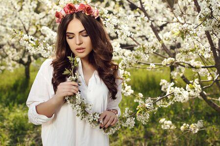 femme brune sexy: mode photo en plein air de la magnifique femme sensuelle avec des cheveux noirs en robe élégante et bandeau de fleurs, posant en fleur jardin