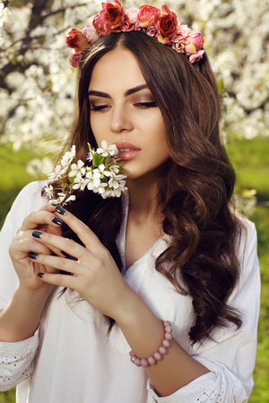 sensual woman: fashion outdoor photo of gorgeous sensual woman with dark hair in elegant dress and flowers headband, posing in blossom garden