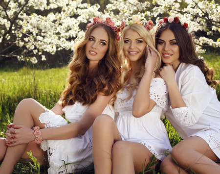 fashion outdoor photo of gorgeous sensual women with dark hair in elegant dresses and flowers headband, posing in blossom garden Stock Photo