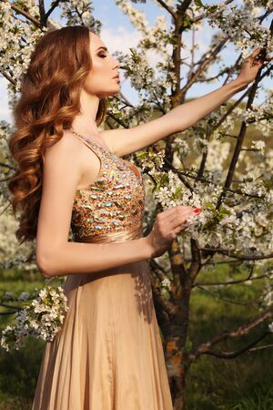 elegant party: fashion outdoor photo of gorgeous sensual woman with dark hair in elegant dress posing in blossom garden