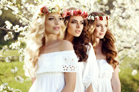 fashion outdoor photo of gorgeous sensual women with dark hair in elegant dresses and flower's headband, posing in blossom garden Stok Fotoğraf