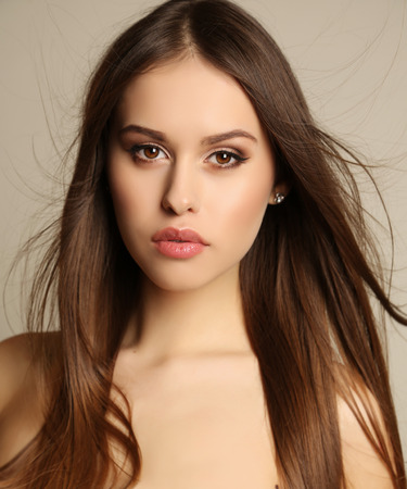 glamour hair: fashion studio portrait of beautiful glamour woman with dark hair and evening makeup